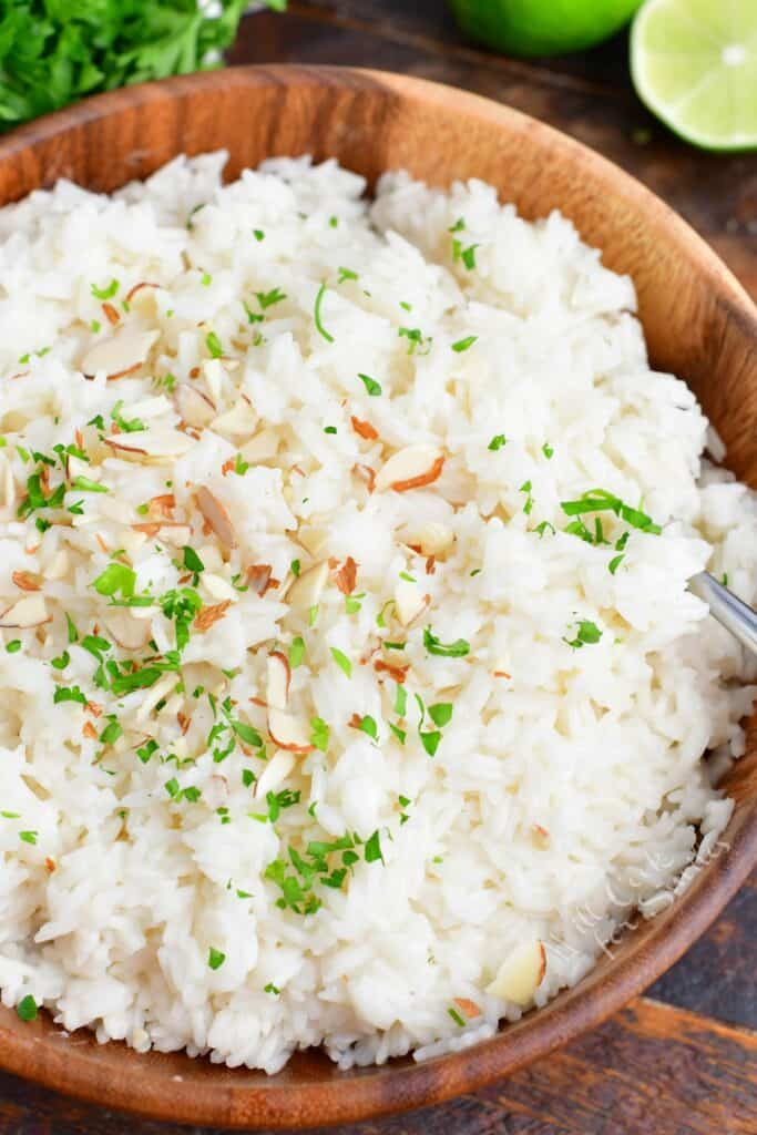Coconut rice is fluffed and presented in a large serving bowl.