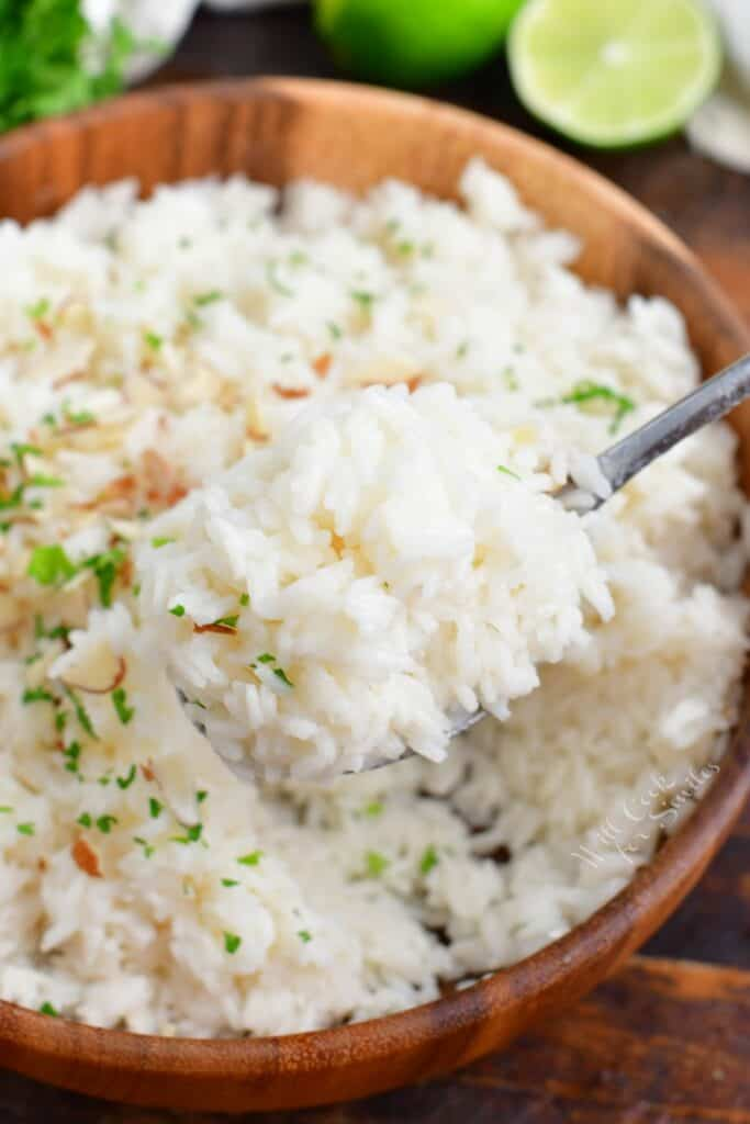 A spoon is lifting a small portion of rice from the bowl.