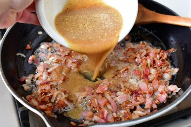 A tangy mixture is being poured onto the cooking bacon.