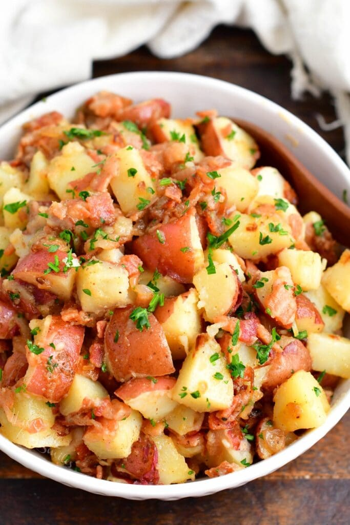 A white bowl is filled with German potato salad.