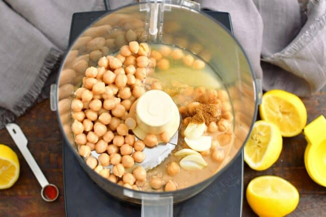 The ingredients for hummus are unblended in a food processor.