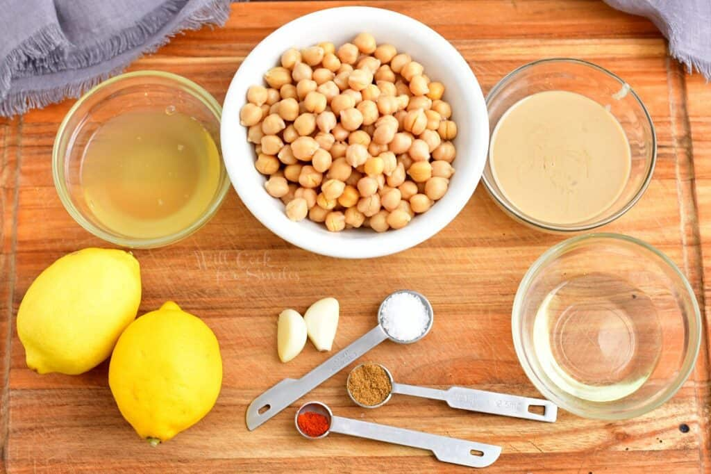 The ingredients for hummus are placed on a wooden cutting board.