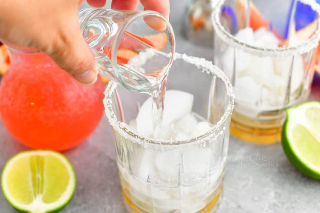 A shot of tequila blanco is being poured into a rimmed glass.