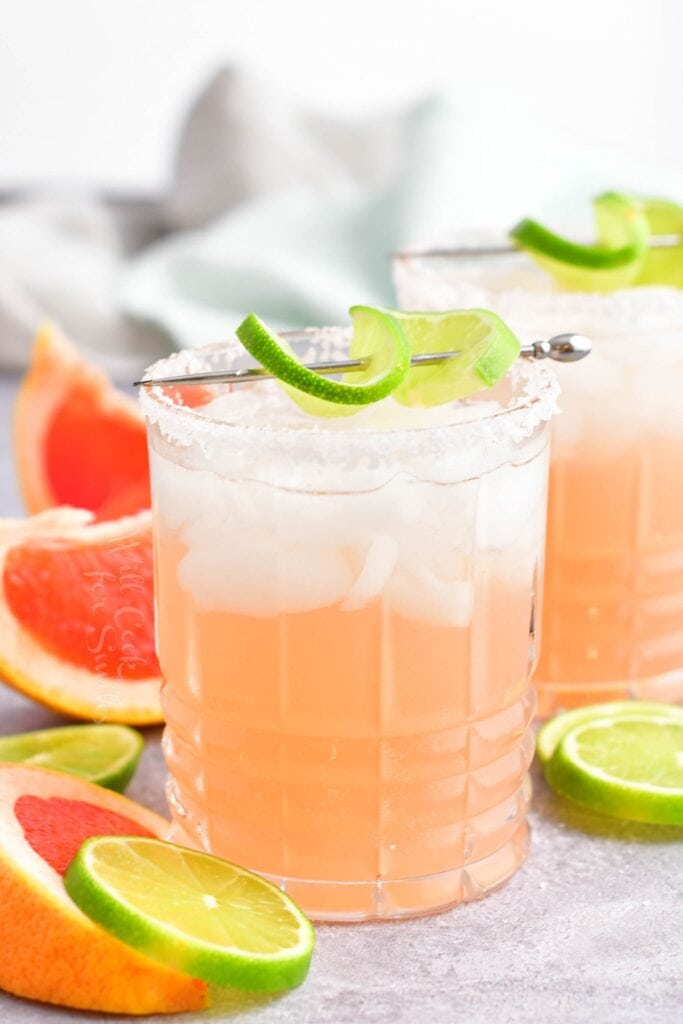 A pink paloma is garnished with lime.