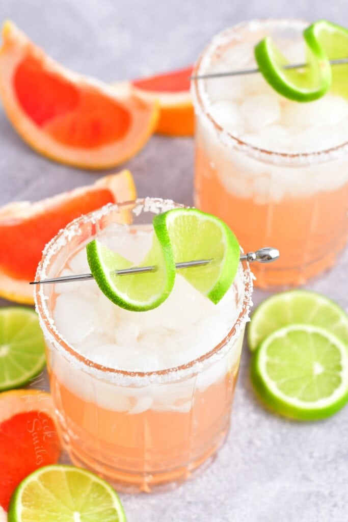 Wedges of lime and grapefruit surround two palomas.
