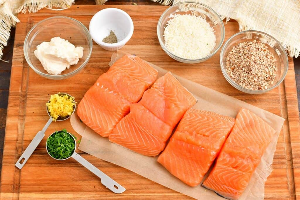 The ingredients for pecan crusted salmon are placed on a wooden cutting board.