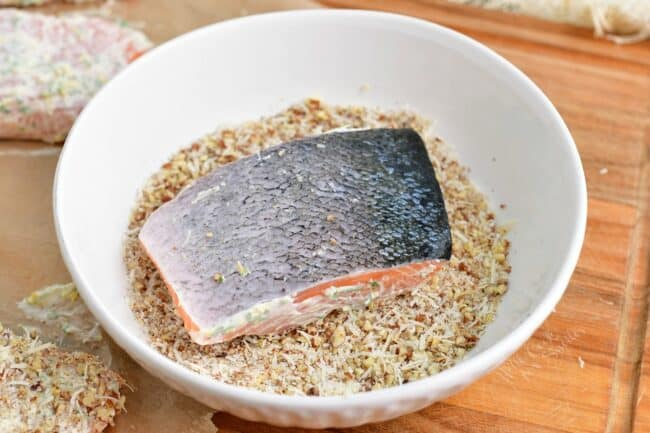 A salmon filet is dipped into pecans and parmesan.
