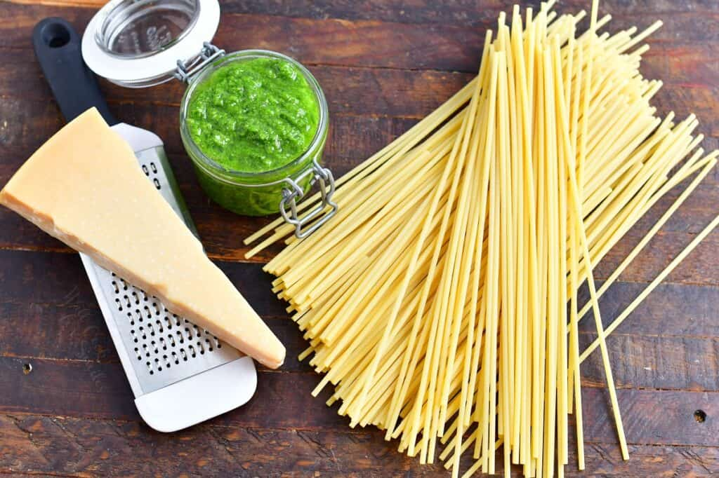 The ingredients for pesto pasta are placed on a wooden surface.