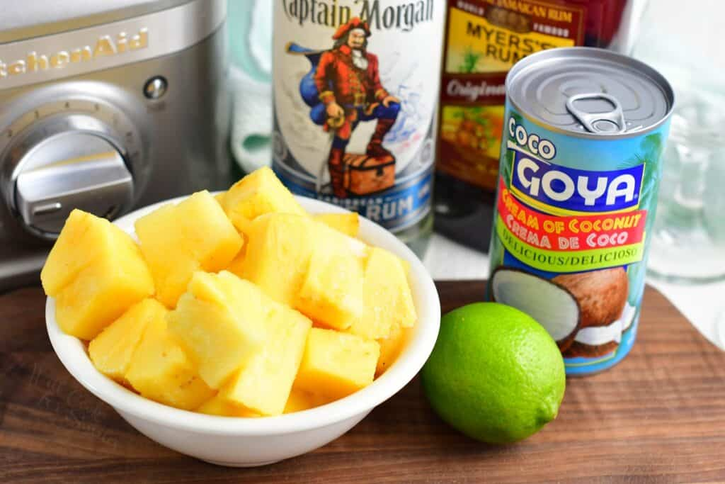 The ingredients for pina coladas are placed on a cutting board.