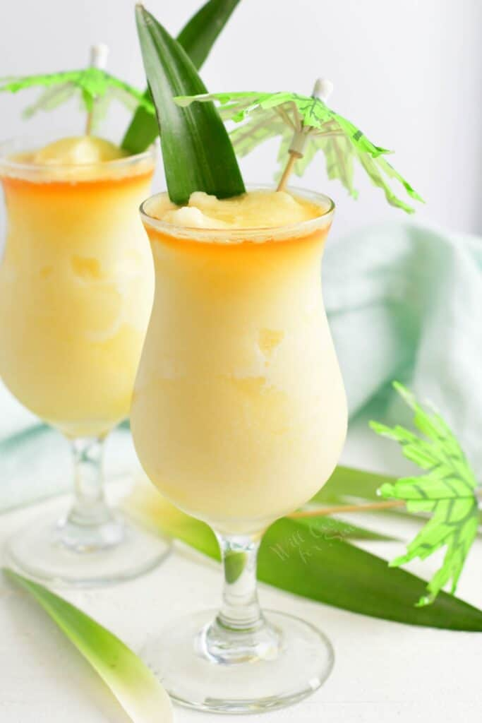 A pina colada is placed on a white surface.