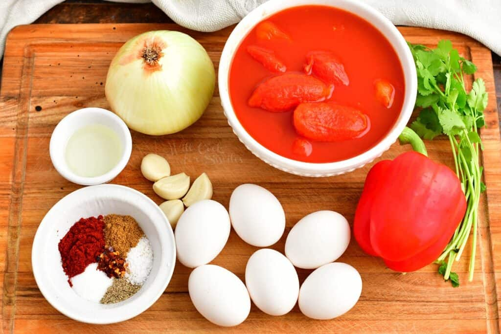 The ingredients for shakshuka are placed on a wooden cutting board.