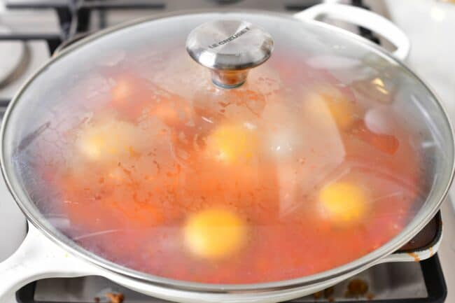A skillet has been covered, showing raw eggs and tomato stew cooking inside.