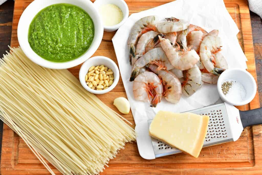 The ingredients for shrimp pesto pasta are placed on a wooden cutting board.