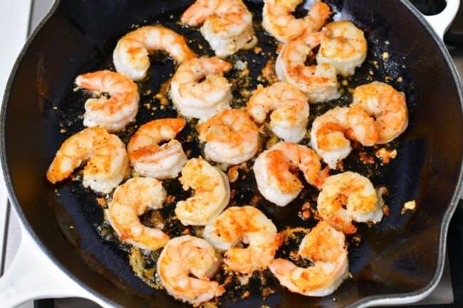 Shrimp is cooking in a large black skillet.