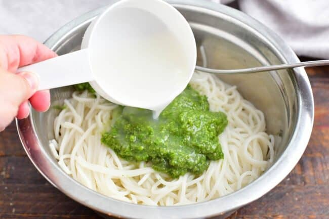 Pasta is topped with green pesto and cooking water.