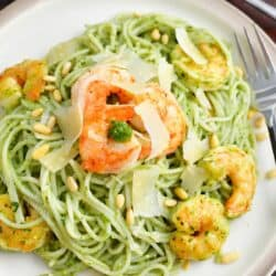 A white plate is filled with pesto pasta and shrimp.