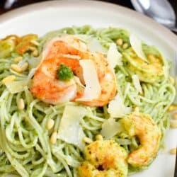 Shrimp and cheese garnish a large potion of pesto pasta.