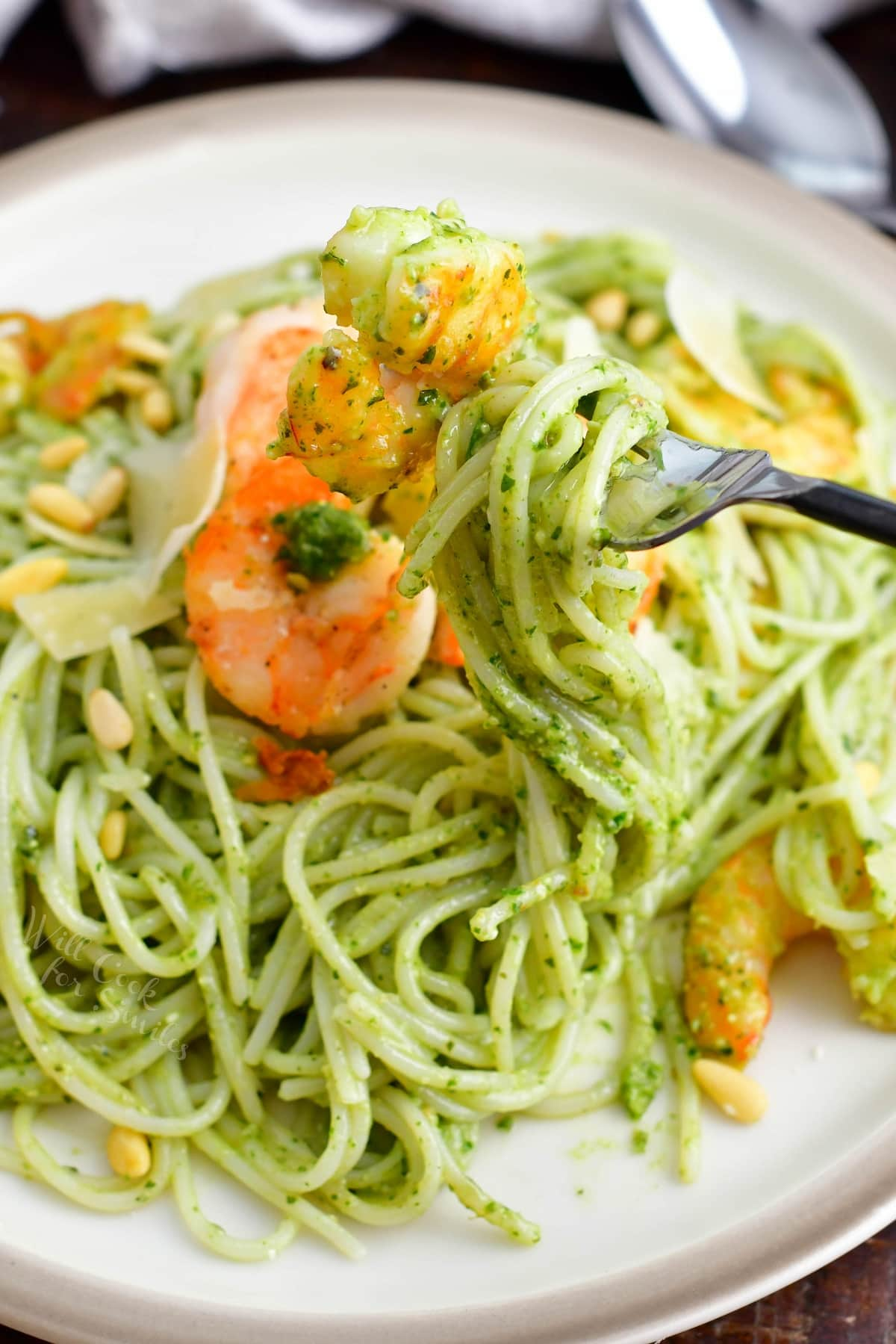 A fork is twirling a bite sized portion of pesto pasta.