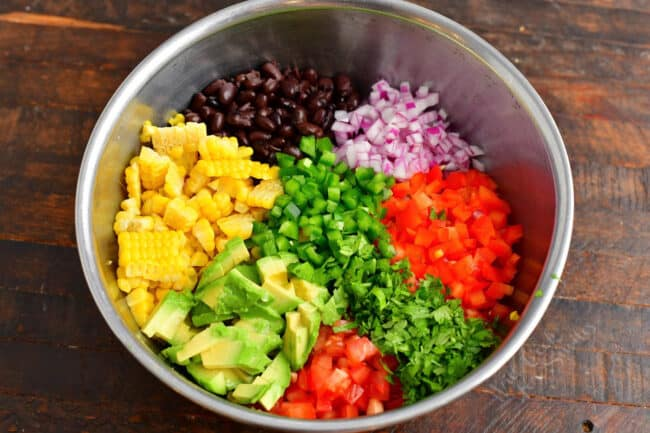 All of the ingredients for corn salad are in a large mixing bowl.