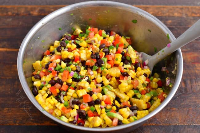Black bean and corn salad has been tossed in a large bowl.