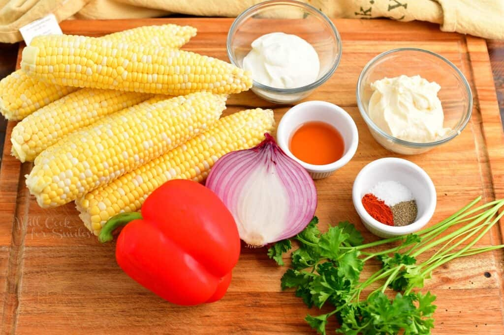 The ingredients for creamy corn salad are placed on a wooden cutting board.