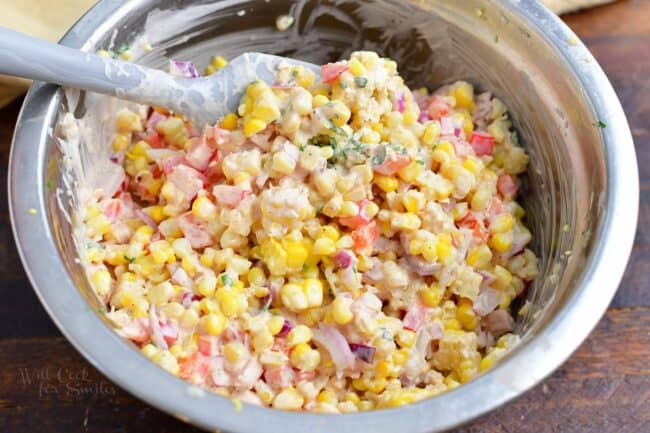 Corn salad is being mixed in a metal bowl.