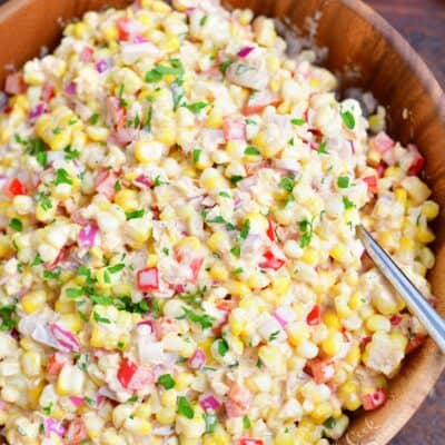 A large wooden serving bowl is filled with freshly made corn salad.