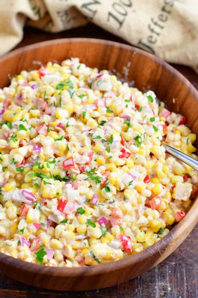 A wooden bowl is filled with creamy corn salad.