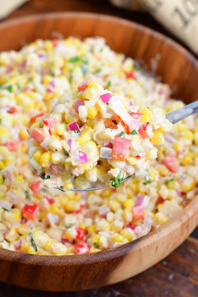A spoonful of corn salad is being lifted from the large bowl.