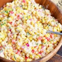 A serving spoon has been placed in the creamy corn salad.