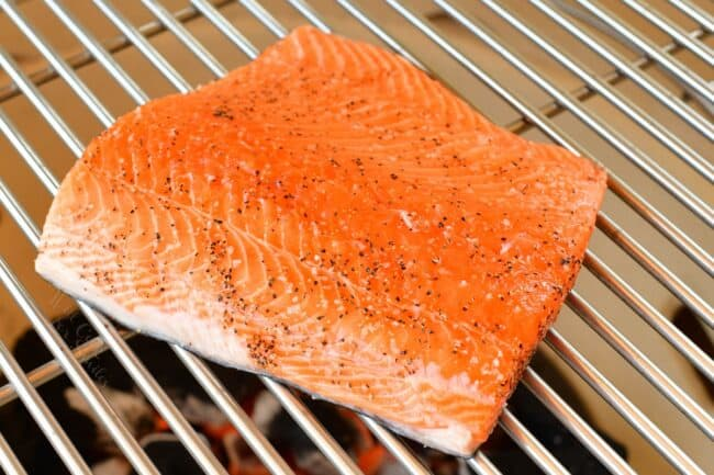 Raw salmon is on a grill.