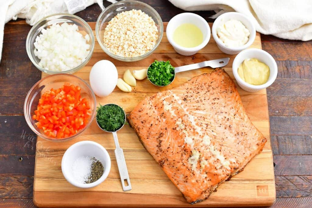 Ingredients for salmon burgers are on a wooden cutting board.