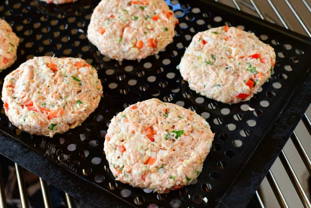 Uncooked patties are on a grill basket.
