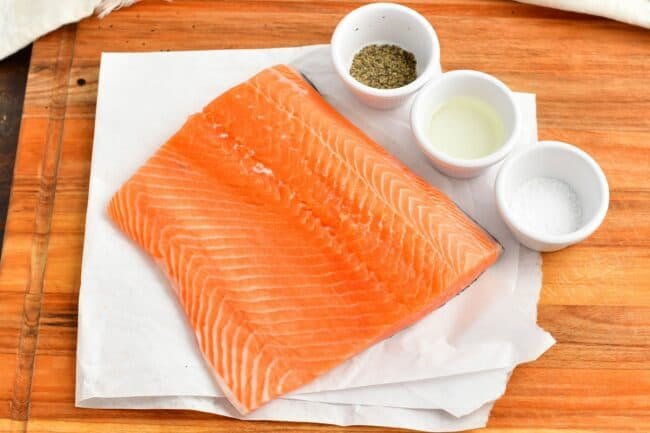 Salmon is placed on a white paper next to cups of seasoning.