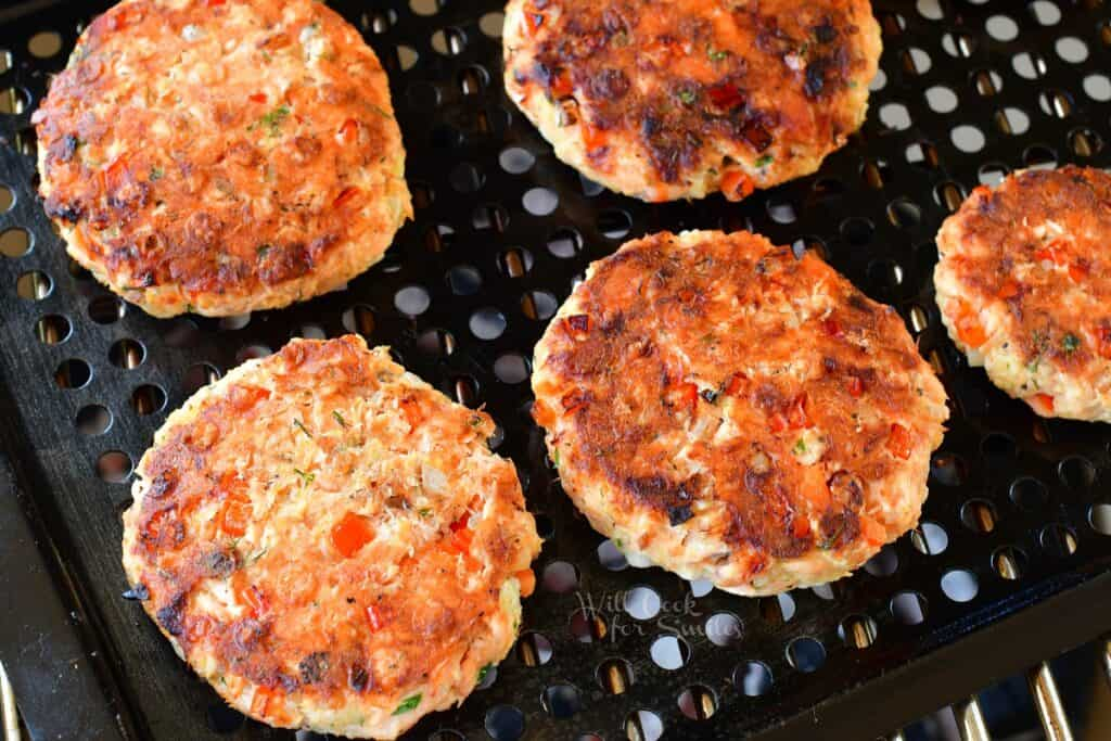 Cooked patties are on a grill.