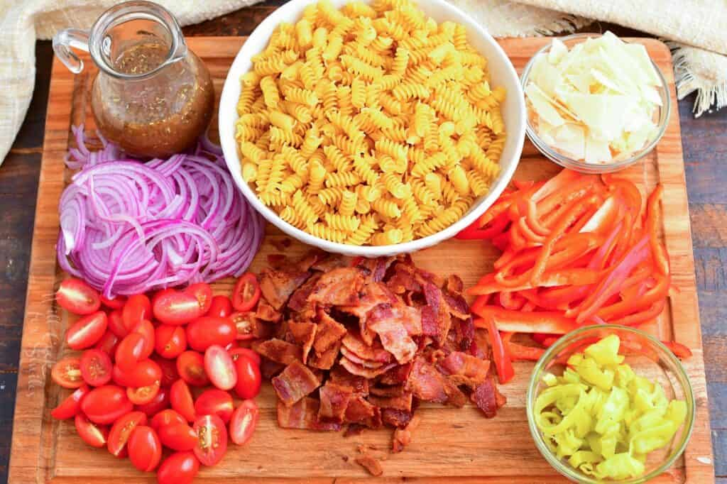 The ingredients for pasta salad are on a wooden cutting board.