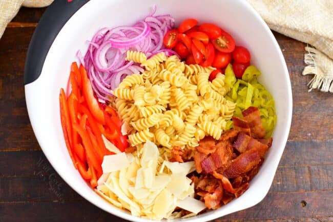 All of the ingredients for pasta salad are in a large white mixing bowl.
