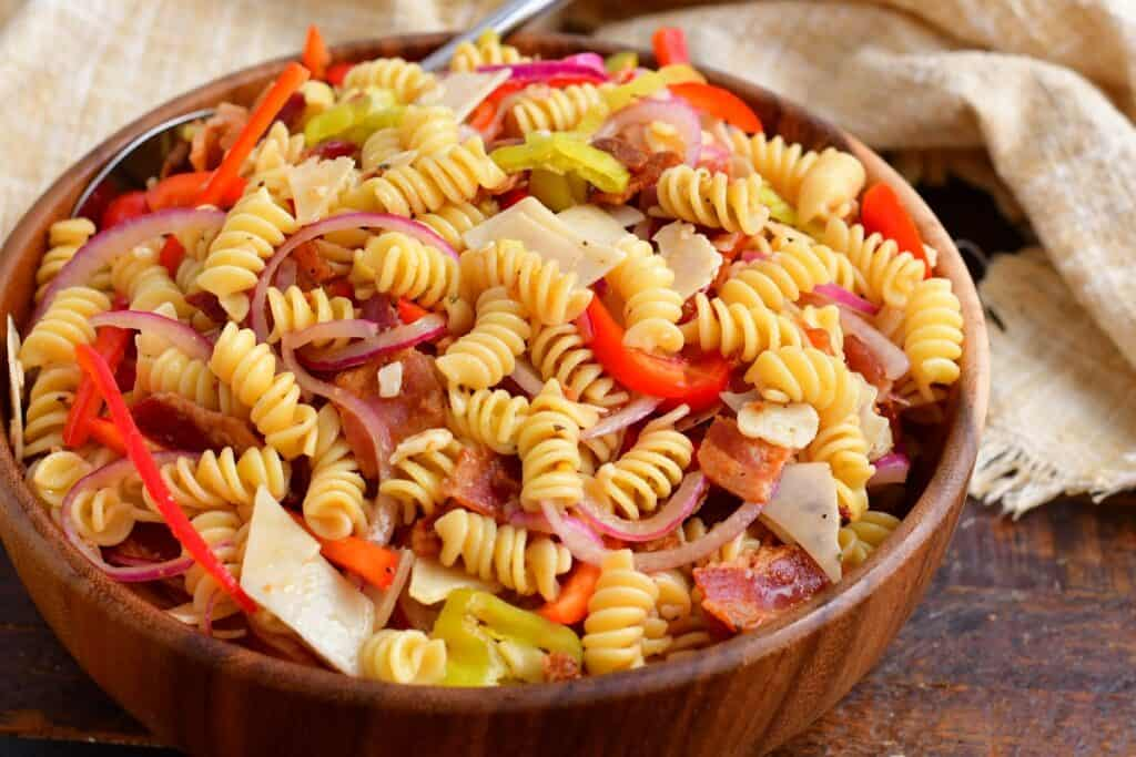 A pasta salad is presented in a large wooden bowl, ready to be served.