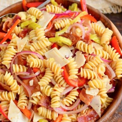 All of the ingredients for pasta salad have been thoroughly tossed in a large bowl.