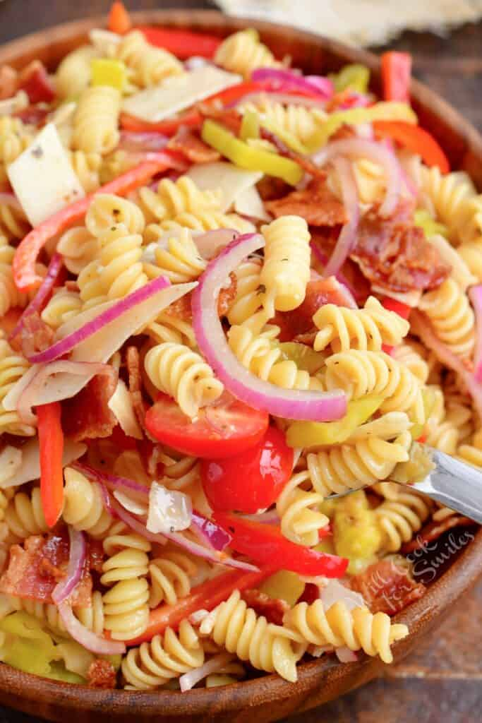 Pasta salad is tossed and presented in a large wooden bowl.