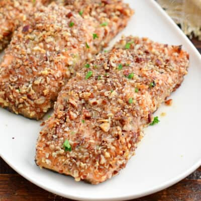 squared off closeup of baked crusted salmon on a white plate