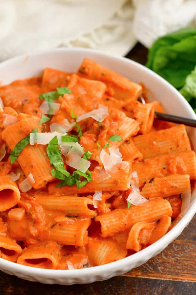 A white bowl filled with pasta is topped with basil and parmesan cheese.