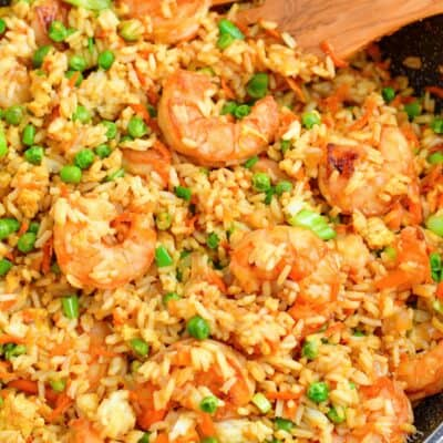 Shrimp fried rice has been cooked in a black skillet and is ready to serve.