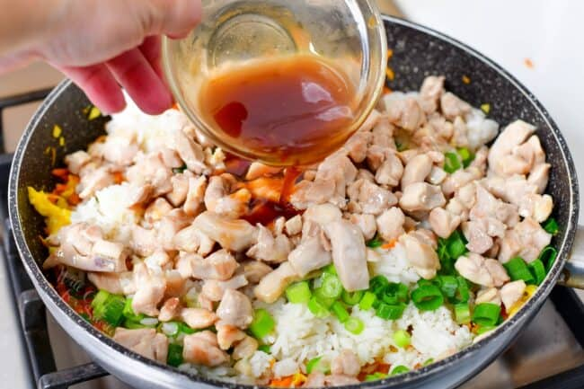 pouring brown sauce into the pan with rice, chicken, and vegetables