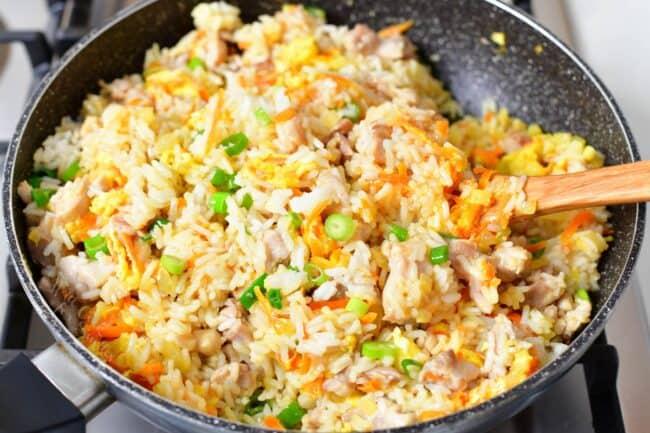 stirring fried rice in a large pan