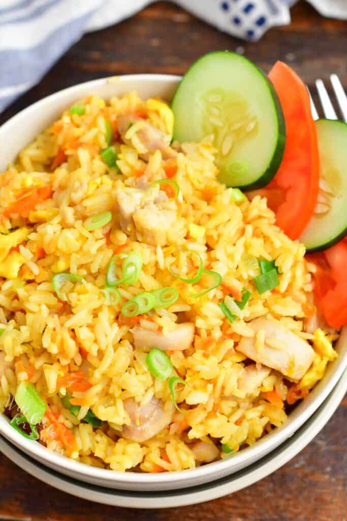 Top view of Thai fried rice in a bowl with cucumber and tomato slices