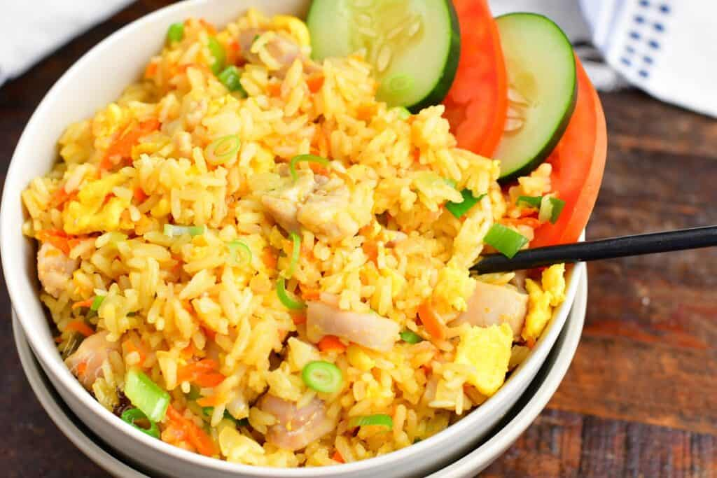 side view of Thai fried rice in a bowl with cucumber and tomato slices