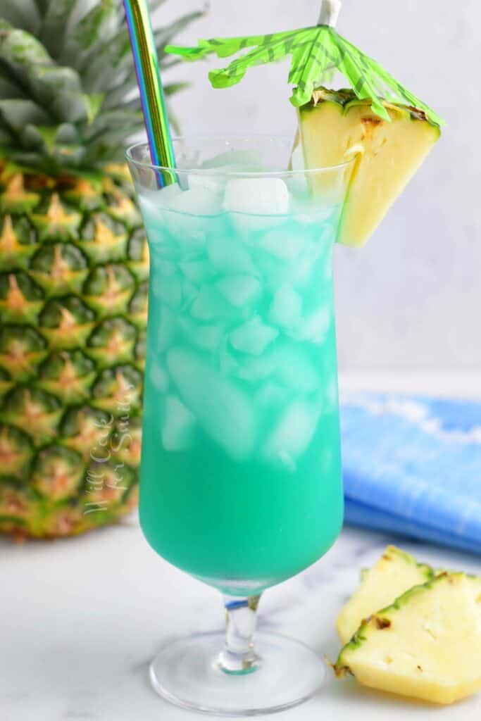 tall hurricane glass filled with blue cocktail