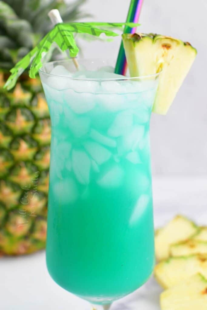 closeup side view of blue cocktail in a glass with pineapple and umbrella