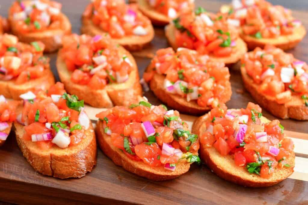 sliced of toasted bread laid out on the cutting board topped with tomato mixture